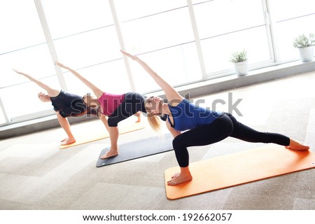 Young people holding triangle pose in a yoga class - stock photo