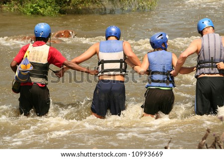 young people in an extreme river crossing adventure - stock photo
