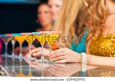 Young people in club or bar drinking cocktails and having fun; close-up on glasses on the bar - stock photo