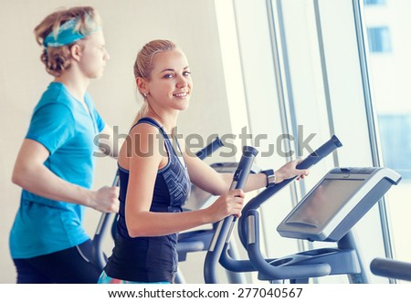 Young people in modern gym on the run simulator - stock photo