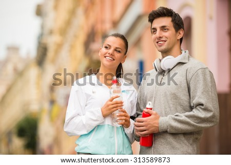 Young people in sportswear with bottles of water are looking away. Outdoor. - stock photo