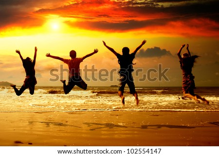 Young people in the beach silhouette - stock photo