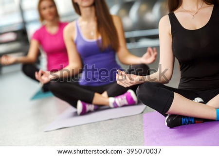 Young people in the lotus position. Group of peaceful people meditating in a yoga studio. Young women doing yoga and meditation in gym for better fitness - stock photo