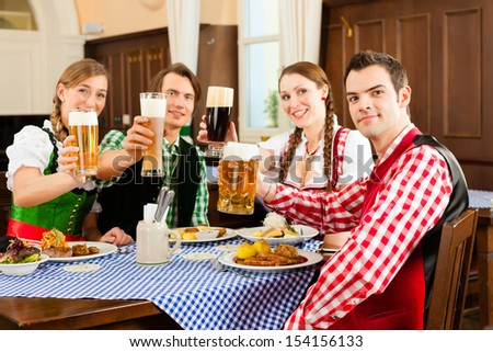 Young people in traditional Bavarian Tracht eating in restaurant or pub lunch or dinner, they toast towards the camera - stock photo