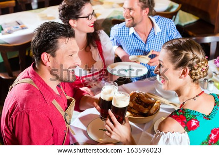 Young people in traditional Bavarian Tracht eating with sausages in restaurant or pub lunch or dinner - stock photo