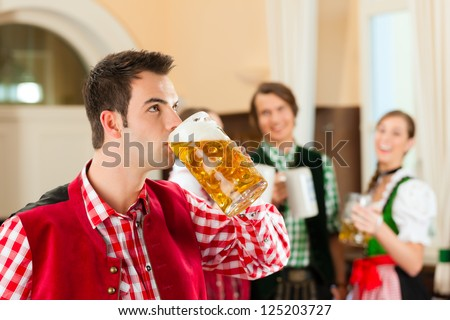 Young people in traditional Bavarian Tracht in restaurant or pub, one man is standing with beer stein in front, the group in the background - stock photo