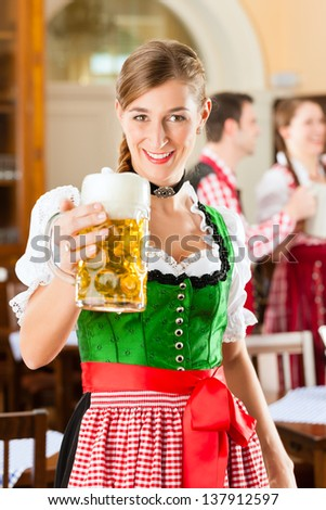Young people in traditional Bavarian Tracht in restaurant or pub, one woman is standing with beer stein in front, the group in the background - stock photo