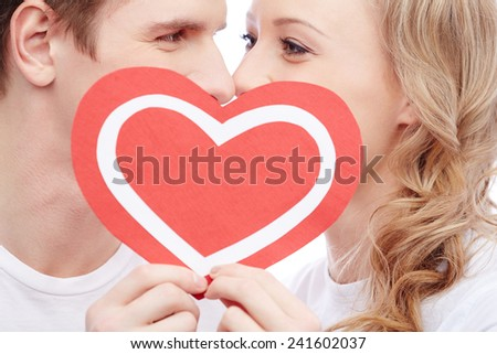 Young people kissing behind paper heart - stock photo
