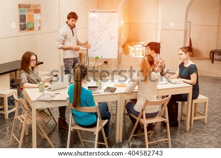 Young People listening Presentation of male Manager active Participants asking Questions in Meeting Room with wood Walls and Table using Flip Chart - stock photo