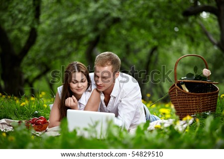 Young people look in the laptop monitor in park - stock photo