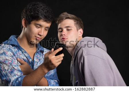 Young people look in the smartphone on a black background - stock photo