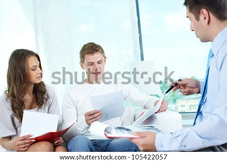 Young people looking through documents to find the best insurance program - stock photo