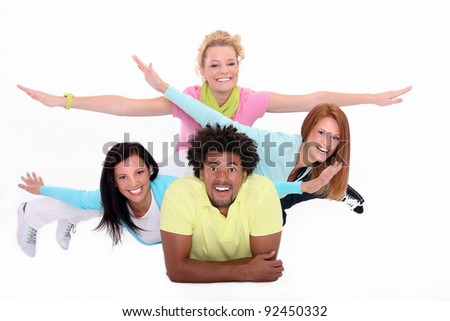 Young people lying down on the white background,gesturing fly. - stock photo