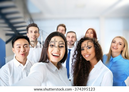 Young people making photo of their self in office - stock photo