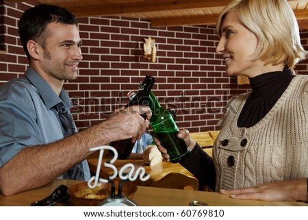 Young people meeting in pub, clinking beer bottles, smiling.? - stock photo