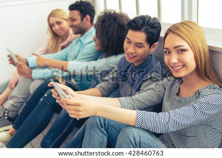 Young people of different nationalities using gadgets and smiling while sitting in a row. Beautiful Asian girl is looking at camera - stock photo