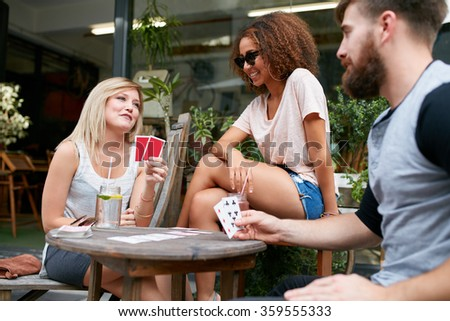 Young people playing cards at sidewalk cafe. Three friends playing poker at outdoor coffee shop. - stock photo