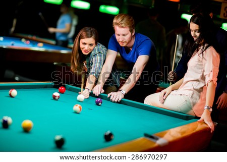 Young people playing pool - stock photo