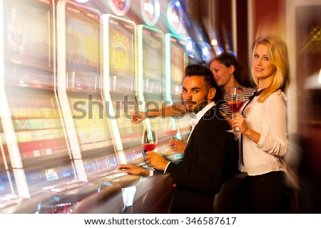 young people playing slot machines in casino - stock photo