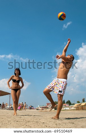 young people playing volleyball on the beach - stock photo