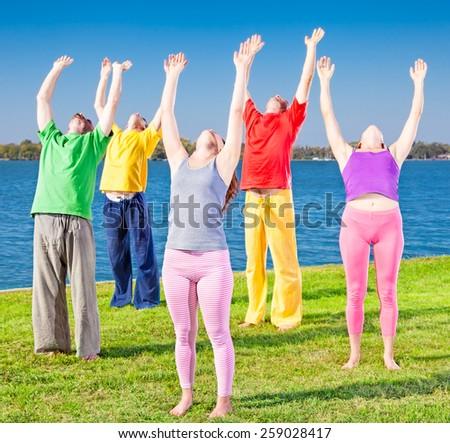 Young people practice Yoga asana on lakeside. Yoga concept. - stock photo