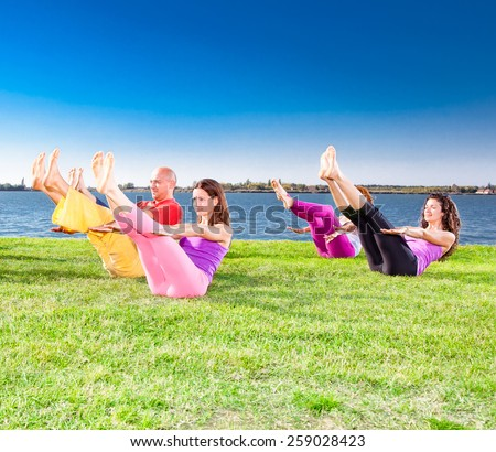 Young people practice Yoga asana on lakeside. Yoga concept. - stock photo