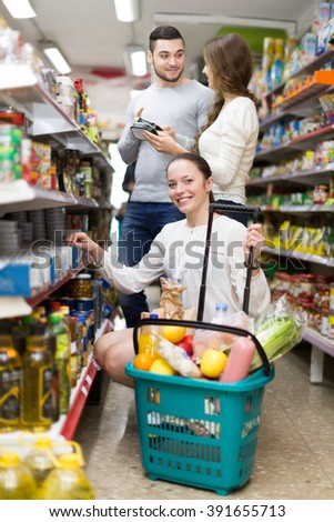 Young people purchasing food for week at supermarket  - stock photo