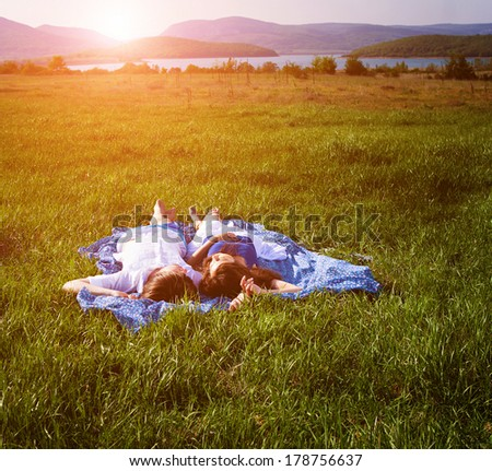 Young people relaxing on the grass near the lake - stock photo