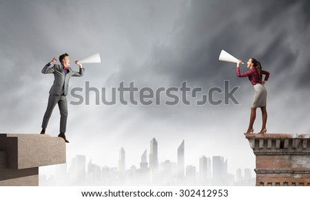 Young people screaming at each other in paper trumpet - stock photo