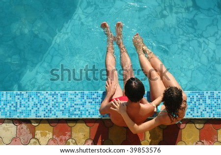 Young people sits beside water pool - stock photo