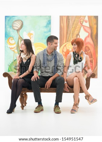 young people sitting on a bench in an art gallery, having a conversation - stock photo