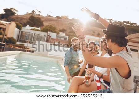 Young people sitting on the edge of the pool enjoying a party. Young woman singing during a the party. Multiracial friends having fun during rooftop party. - stock photo