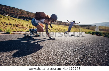 Young people skateboarding outdoors on the road. Young man and woman practicing skating on a rural road. - stock photo