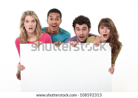 Young people standing behind a blank sign - stock photo