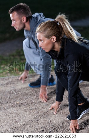 Young people starting running in park at evening - stock photo