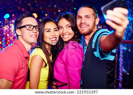 Young people taking selfie at nightclub - stock photo