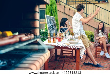 Young people talking outdoors and meal cooking in furnace - stock photo