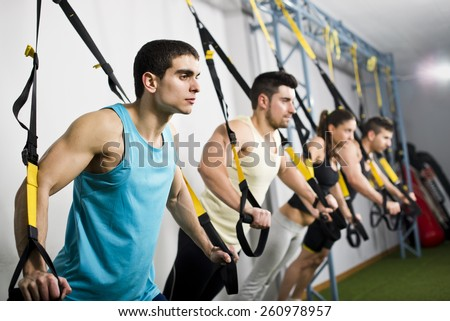 Young people training in elastic rope at fitness gym center - stock photo