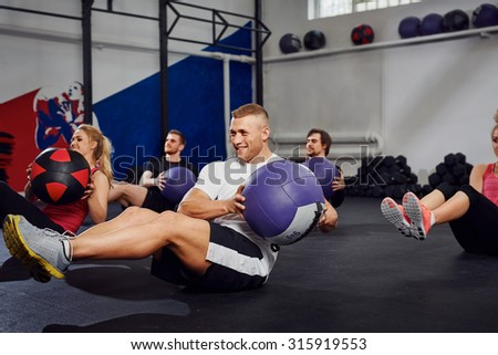 young people training with exercise ball at gym - stock photo