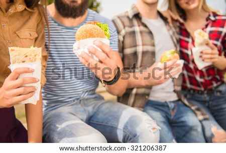 Young people walking outdoors. Sitting in the park and eat fast food - stock photo