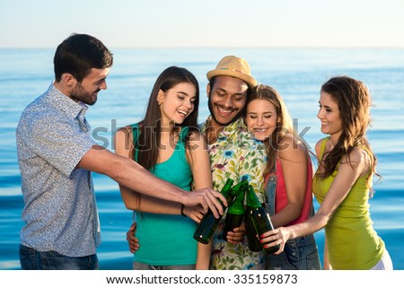 Young people with a beer on the background of the sea. Cheerful young people drinking beer on vacation. Young people drink alcohol at the resort. Young people celebrate birthday. - stock photo