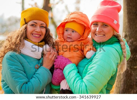 young people with little child in the park autumn posing - stock photo