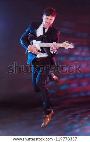Young performer with guitar gives his best - stock photo
