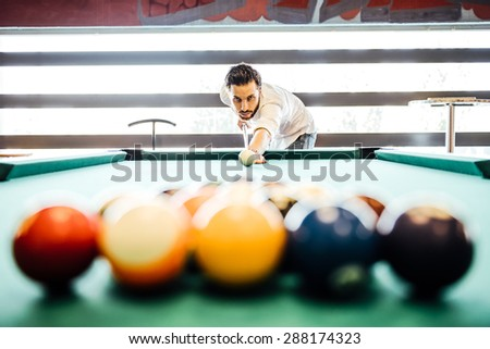 Young Person Playing Snooker - Man Lining To Hit Ball On Pool Table - stock photo