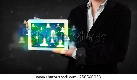 Young person presenting tablet with green social media icons and symbols - stock photo