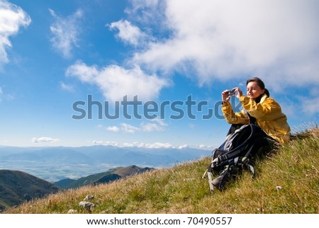 Young person relaxes on hiking in mountains and taking photo with mobile phone - stock photo