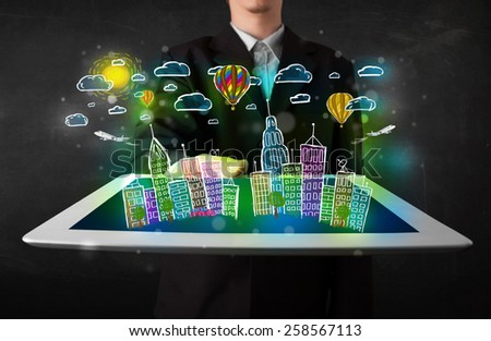 Young person showing tablet with hand drawn colorful cityscape - stock photo
