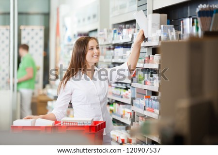 Young pharmacist stocking shelves in pharmacy - stock photo