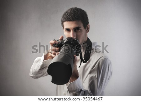 Young photograph holding a camera - stock photo