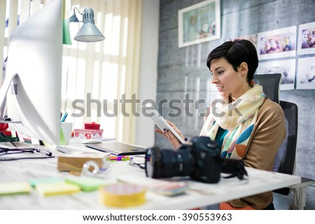 Young photographer and graphic designer at work in office - stock photo